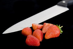 Fresh Strawberries with a knife. On a black background Royalty Free Stock Photography