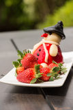 Fresh strawberries and marzipan on a rustic wooden garden table Royalty Free Stock Image
