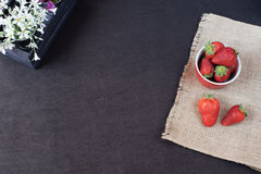 Fresh strawberries in mini metal bucket on hessian jute. White and purple flowers in a decorative wooden crate. Black background. Royalty Free Stock Photography