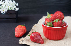 Fresh strawberries in mini red bowl on hessian jute. White and purple flowers in a decorative wooden crate. Black background Stock Photo