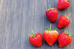 Fresh strawberries on old wooden background. Fresh strawberries on old black wooden background. Top view with copy space. nature fruit concept and healty eating Stock Images