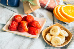 Fresh strawberries and oranges and bananas on plate Royalty Free Stock Photos