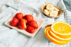 Fresh strawberries and oranges and bananas on plate Stock Photos