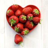Fresh strawberries on a plate in the shape of heart Stock Images