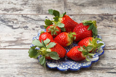 Fresh strawberries on a plate. On wooden table Royalty Free Stock Images