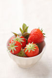 Fresh strawberries in a porcelain bowl on linen tablecloth Royalty Free Stock Images