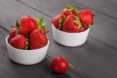 Fresh strawberries in portion bowls. On dark wooden background Stock Images
