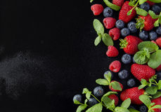Fresh strawberries, raspberries and blueberries on a black background. Selective focus, space for text Stock Photos