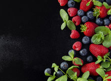 Fresh strawberries, raspberries and blueberries on a black background. Selective focus, space for text Royalty Free Stock Photography