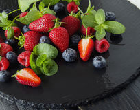 Fresh strawberries, raspberries and blueberries on a black background. Selective focus, space for text Royalty Free Stock Image