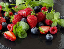 Fresh strawberries, raspberries and blueberries on a black background. Selective focus, space for text Stock Images