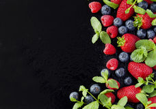 Fresh strawberries, raspberries and blueberries on a black background Stock Photos