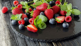 Fresh strawberries, raspberries and blueberries on a black background. Selective focus, space for text Royalty Free Stock Photo
