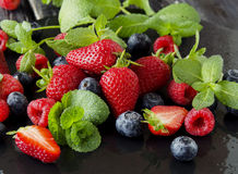 Fresh strawberries, raspberries and blueberries on a black background. Selective focus, space for text Stock Photo