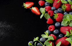 Fresh strawberries, raspberries and blueberries on a black background. Selective focus, space for text Royalty Free Stock Photos