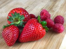Fresh Strawberries and Raspberries on a cutting board. Fresh Strawberries and Raspberries on a wooden butcher block Royalty Free Stock Images