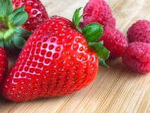 Fresh Strawberries and Raspberries on a cutting board. Fresh Strawberries and Raspberries on a wooden butcher block Stock Images