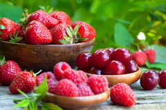 Fresh strawberries, raspberries and sour cherries. In old wooden bowls Royalty Free Stock Images
