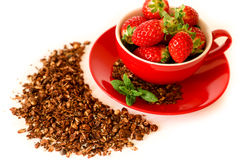 Fresh strawberries in a red bowl and chocolate granola  on white background. Stock Photo