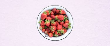 Fresh strawberries in retro bowl, organic food, textured background with Pink Lavender color toning, top view. Fresh strawberries in retro bowl, textured stock images