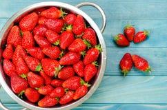 Fresh strawberries in retro colander on rustic aqua blue wooden Stock Image