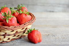 Fresh strawberries. Ripe juicy strawberries in a wicker basket and on a vintage wooden table. Natural source of vitamins Stock Images