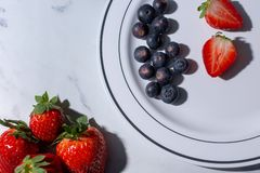 FRESH STRAWBERRIES AND SANDWICHES CUT IN WHITE PLATE ON BLACK BACKGROUND royalty free stock image
