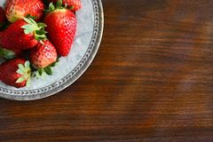 Fresh strawberries on a saucer. Flat lay strawberries on a saucer on a brown table, red ripe fruit, delicacy Stock Images