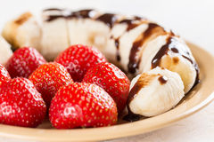 Fresh strawberries with sliced banana and topped chocolate cream.  Stock Photography