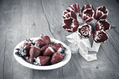 Fresh strawberries and spring tulips Stock Photos