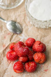 Fresh strawberries with sugar and sugar bowl on the wrinkled brown pack paper Stock Images