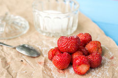 Fresh strawberries with sugar and sugar bowl on the wrinkled brown pack paper Stock Photography
