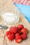 Fresh strawberries with sugar and sugar bowl on the wrinkled brown pack paper Royalty Free Stock Images