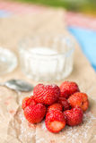 Fresh strawberries with sugar and sugar bowl on the wrinkled brown pack paper Royalty Free Stock Photography