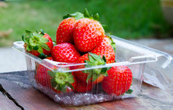Fresh strawberries on the table and inside plastic box Royalty Free Stock Photo