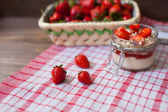 Fresh strawberries on the tablecloth and in the basket Royalty Free Stock Photo