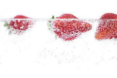 Fresh Strawberries in Water. Juicy red strawberries plunging into some carbonated water. Shallow depth of field stock images