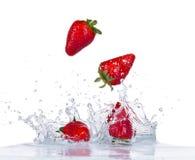 Fresh strawberries in water splash on white Stock Photography