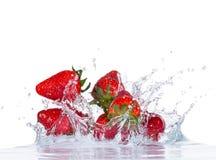 Fresh strawberries in water splash on white Stock Photos