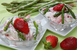 Fresh strawberries in white cream with green aspar stock images