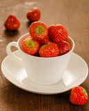 Fresh strawberries in white cup. On an old wooden table top Stock Images