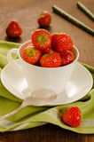 Fresh strawberries in white cup. On an old wooden table top Royalty Free Stock Images