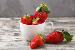 Fresh strawberries in a white cup on wooden background Stock Images