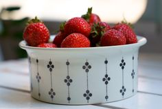 Fresh strawberries in a white cup on a wooden table stock image