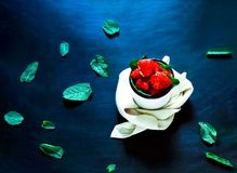 Fresh strawberries in white metal cup with leaves of mints on dark background. Organic food concept. royalty free stock photos