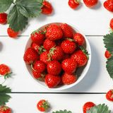 Fresh strawberries in a white porcelain bowl on wooden table in. Rustic style Royalty Free Stock Photography
