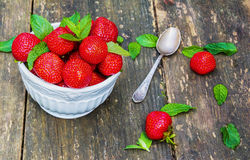 Fresh strawberries in white vintage bowl on old wooden table. Green mint leaves and ripe berries from garden Stock Photo
