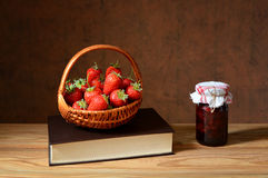 Fresh strawberries in of wicker basket, books and jam Royalty Free Stock Images