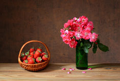 Fresh strawberries in of wicker basket and flowers Royalty Free Stock Photos