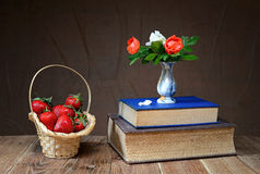 Fresh strawberries in a wicker basket and flowers in a vase Royalty Free Stock Photo